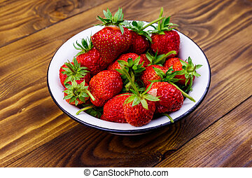 Fresh ripe strawberry in white bowl on a wooden table