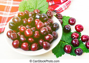 Fresh ripe sweet cherry in a plate on a light table