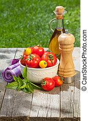 Fresh ripe tomatoes, olive oil bottle, pepper shaker and ...