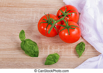 Fresh ripe tomatoes with basil leaves in the wood background