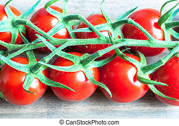 Fresh ripe vine tomatoes with a shallow depth of field on a wood