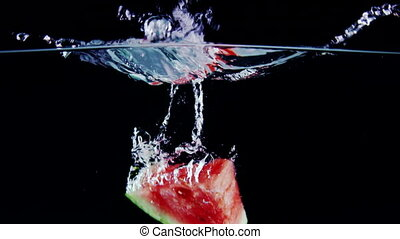 Fresh ripe watermelon slice falls into water with splashes