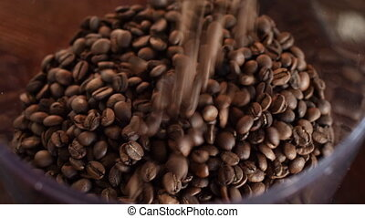 Fresh roasted coffee beans poured in a grinder from a glass jar.