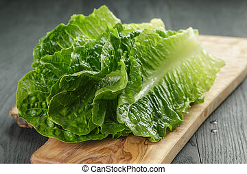 fresh romain green salad leaves on olive board on wood table,