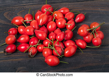 fresh rose hips on a dark wooden background