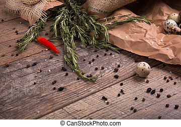 Fresh rosemary herbs. Red hot chili pepper. Egg with black pepper. Many spices on a rustic background. Mexican cuisine.