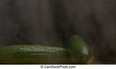 Fresh rotating vegetables cucumbers on a black background in the smoke from which evaporation goes, close-up, slow motion