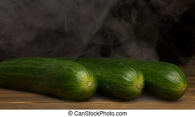 Fresh rotating vegetables cucumbers on a black background in the smoke from which evaporation goes, close-up, slow motion, vegan