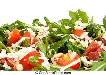 Fresh rucola lettuce with tomatoes, pine kernels and Parmesan cheese over white background