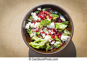 Bowl of fresh salad with lettuce, fetta cheese, pomegranates and more