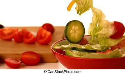 Fresh salad falling into bowl