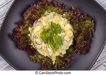 Fresh salad from a radish, green onion, potato, cucumber and boiled egg with mayonnaise on lettuce leaves. Top view