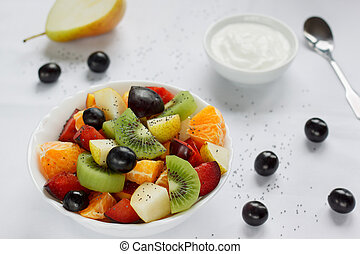 Fresh salad from kiwi, oranges, plums and other fruits. Healthy lifestyle.