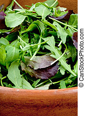 fresh salad mix in wooden bowl close up
