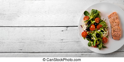 fresh salad mix with grilled salmon fillet on white wooden table. top view copy space