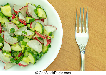 Fresh salad of cucumbers and radishes in a dish on a wooden table with fork