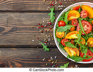 Fresh salad of red, pink and yellow tomatoes with arugula and spices in a white plate on a dark wooden table. Copy space. Top view. Selective focus