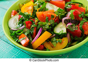 Fresh salad of tomatoes, cucumbers, peppers, arugula and red...
