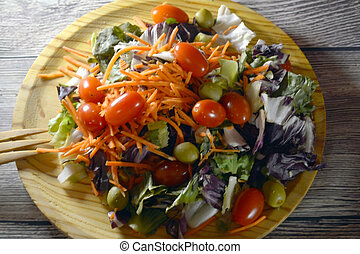 Fresh salad on a wooden plate