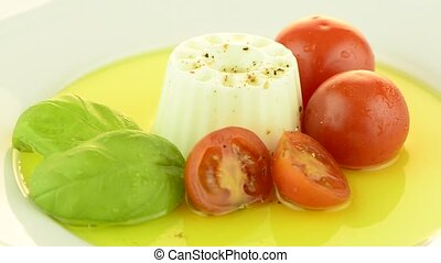 Fresh salad with goat cheese, tomato and basil pesto on a...