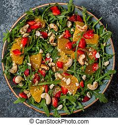 Fresh salad with arugula, fruits and nuts.