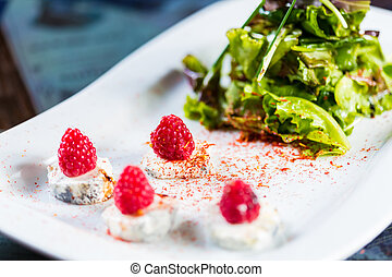 fresh salad with goat cheese and raspberry.