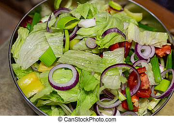 fresh salad with lettuce, tomatoes, cucumbers and a ring of red onions in an iron bowl top view