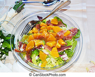 fresh salad with orange slices, lettuce, bacon pieces and sweetsour sauce