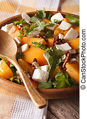 Fresh salad with persimmon, arugula and cheese close up. vertical