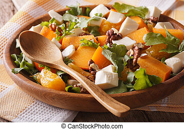 Fresh salad with persimmons, walnuts, arugula, cheese close-up.