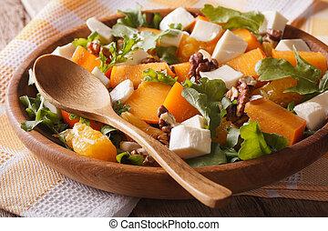 Fresh salad with persimmons, walnuts, arugula, cheese close-up.