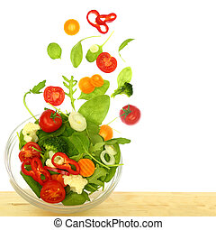 Fresh salad with pieces flying out of a bowl isolated