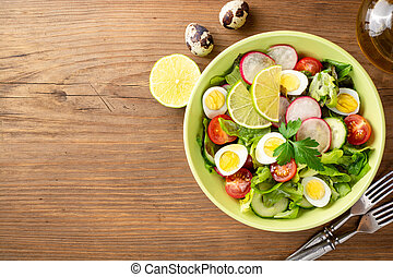 Fresh salad with vegetables and quail eggs on rustic wooden background