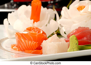Platter of Asian tuna and salmon sashimi with dicon radish flowers