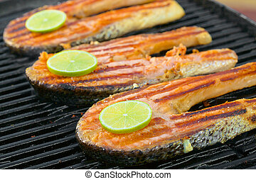 Fresh salmon fillet with lime cooked on a grill