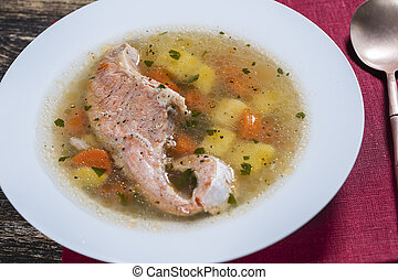 Fresh salmon fish soup with carrots and potatoes in a white plate, close up