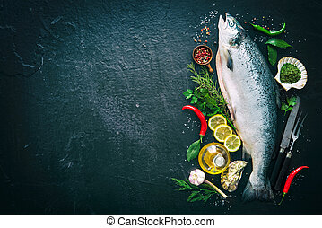 Fresh salmon fish with seasoning on black stone