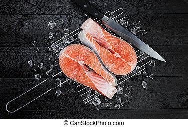 Fresh salmon steak on black background, top view