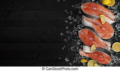 Fresh salmon steaks on black background, piece of chilled red fish on ice, top view
