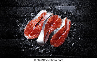 Fresh salmon steaks on black wooden background. Top view