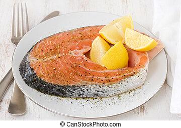 fresh salmon with lemon on white plate