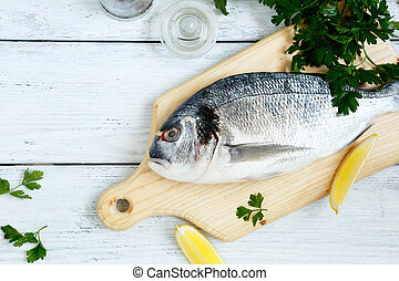 Fresh sea bream and paper on wooden board, top view