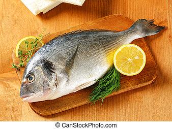 Fresh sea bream on cutting board - Fresh sea bream and lemon...