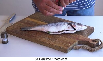 fresh sea fish preparation - someone hands seasoning raw...