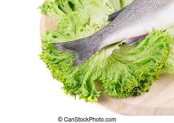 Fresh seabass fish tail on lettuce.