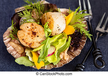 Fresh seared sea scallops salad with mango, radish, avocado on scallop shell
