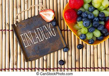 fresh seasonal fruits and a metal sign on a bamboo mat,...