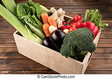 fresh seasonal vegetables in wooden box on wooden table background