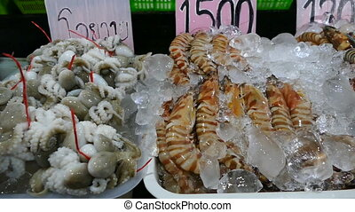 Fresh shrimp and squid on ice in a fish stall at the market...
