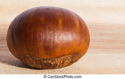 Fresh single chestnut on the wooden